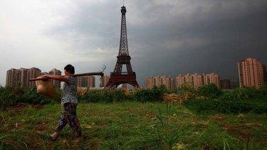 A farmer walks past a replica of the Eiffel tower at a development in Tianducheng.