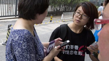 Women's rights activist Wei Tingting, right waits outside a court where the first court case in China involving so-called conversion therapy was held last July in Beijing.