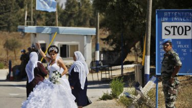 An Israeli-Druze bride crosses the United Nations buffer zone from Israel into Syria in the disputed Golan Heights for her wedding. Once across, she is not allowed back.