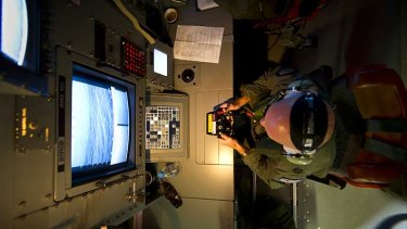 The hunt for debris: Warrant Officer Michael Wright uses scanners aboard an RAAF Orion aircraft.