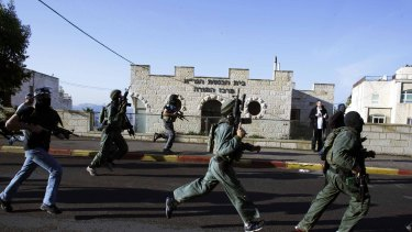 Israeli security personnel run next to the synagogue, where the attack took place.