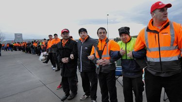 Hundreds of workers form a picket line.