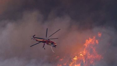 """An apocalypse"" ... a helicopter tries to put out a fire as it moves towards Colorado Springs."