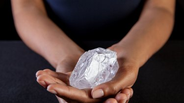 A Sotheby's employee in New York holds the Lesedi La Rona - the largest diamond discovered in more than a century.