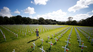 Children walk through a field of memorial crosses on the lawn in front of the Auckland War Memorial Museum in Auckland, New Zealand. The field of white crosses has been installed in the lead up to ANZAC Day.