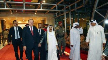 Turkish President Recep Tayyip Erdogan, second left, walks with the Emir of Kuwait Sheikh Sabah al-Ahmad al-Sabah, center, prior to their meeting in Kuwait City on Sunday.