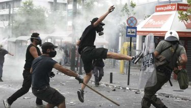 Greek protestors fight police as the parliament votes in favour of a new austerity package.