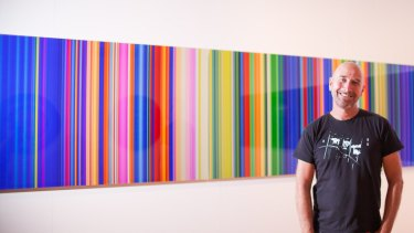 Artist Paul Snell with the artwork he created for the Sensis marquee.