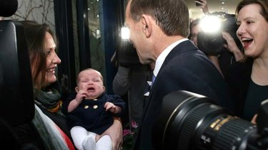 Opposition Leader Tony Abbott meets a mother and her baby during the election campaign as his signature paid parental leave scheme faces hostile MPs worried about budget cuts.