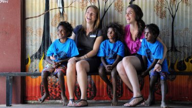 Teachers Nicole Peeler and Naomi Gibb, with students from the Aurukun school, are in no hurry to leave their Cape York jobs.