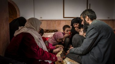 Younes Omar and his family, who reportedly escaped one of the last contested areas of Raqqa, break bread at a mosque  being used as a reception centre  on the outskirts of  the city.