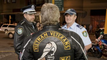 Outlaw Motorcycle Club members gather on Bayswater road as police look on.