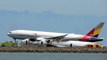 An Asiana Airlines plane flies over the wreck of Flight 214.