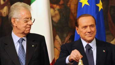 Italy's new Prime Minister Mario Monti (L) prepares to be given the bell from outgoing prime minister Silvio Berlusconi, marking the moment he takes office.