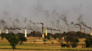 Chimneys of brick kilns emit smoke on the outskirts of New Delhi, India. Countries around the world have been missing their CO2 emissions targets.