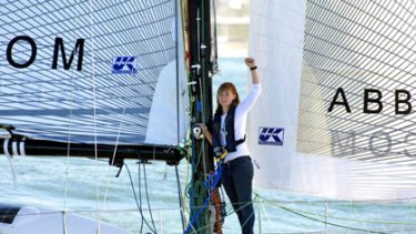 Abby Sunderland waves aboard her boat, Wild Eyes.