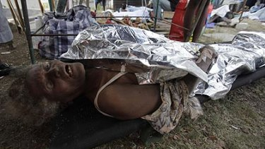 Ms Zizi, 69, lies on a stretcher after being pulled from the rubble of the collapsed cathedral.