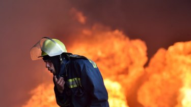 A Ukrainian firefighter retreats from the fire at the fuel depot outside Kiev.