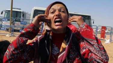 """Syrian Kurdish refugee from Kobani, Zozan Nahsan, 21, shouts her anger, """"where are the big powers, where is humanity? They kill us, Kobani is being massacred."""""""