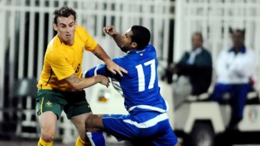 Socceroos midfielder Luke Wilkshire looks to break clear of his Kuwaiti opponent.