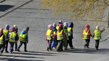 A group of nursery school children in yellow vests out for a walk in Stockholm.