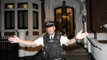 A police officer gestures outside Ecuador's embassy housing Julian Assange
