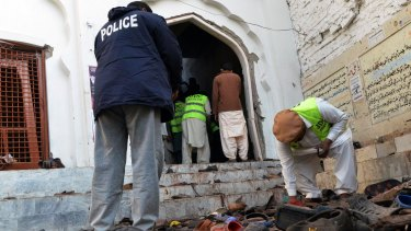 Pakistani police gather evidence following the bomb attack on a Shiite mosque.