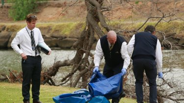 Police investigating the death of Brendan Bernard take away evidence from the banks of the Maribyrnong River.