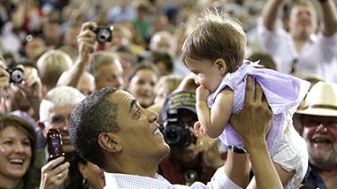 Barack Obama lifts 11-month-old Katirie Duran during a town hall meeting in Montana to sell his health-care reform package, which has been jeopardised by the right.