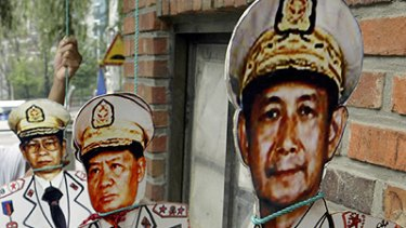 Paper tigers? ... a protester's cut-out pictures of Burmese leaders.
