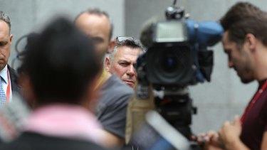 Chief of Staff Rob Messenger listens as Tasmanian Senator Jacqui Lambie addresses the media during a press conference.