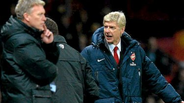Tight race: Arsenal manager Arsene Wenger reacts at Old Trafford as Manchester United manager David Moyes looks on.