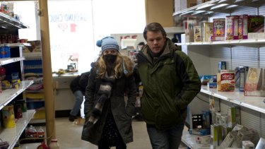 In search of a story: A worried dad (Matt Damon) leads his kid through the dull shambles of <i>Contagion</i>.