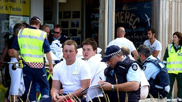 Police question survivors after a man drowned when a boat capsized off Port Phillip Bay.