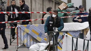 Looking for evidence ... police officers gather at the site of a shooting in Toulouse