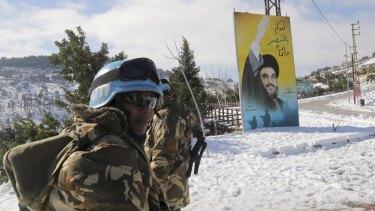 UN peacekeepers in Lebanon stand next to a banner for Lebanon's Hezbollah leader Hassan Nasrallah in snow-covered Kfar Kila village near the Lebanese-Israeli border.