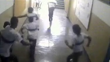 An image taken from a security camera video distributed by the Rio police shows students of the Tasso da Silveira school running from the classroom where a gunman opened fire on them.