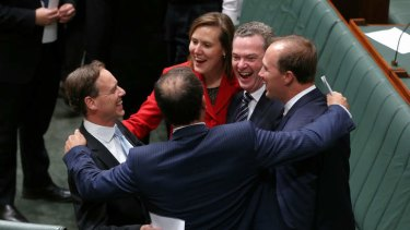 Environment Minister Greg Hunt (left) is congratulated by colleagues including Christopher Pyne and Kelly O'Dwyer.