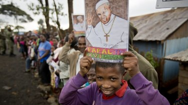 A boy holds a picture of Pope Francis as he awaits his arrival at the Kangemi slum in Nairobi.