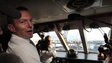 Tony Abbott at the helm of Green Island Reef Tours' big catamaran in Cairns this morning.