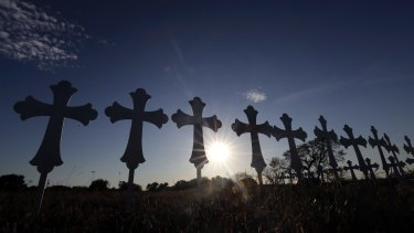 The sun sets behind 26 crosses placed in a field before a vigil for the victims of the First Baptist Church shooting in Sutherland Springs, Texas.