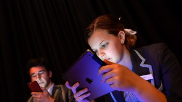 Teenagers spending too much time on electronic devices is raising concerns about inactivity and obesity. Sienna Withington and Daniel Marks using their devices.