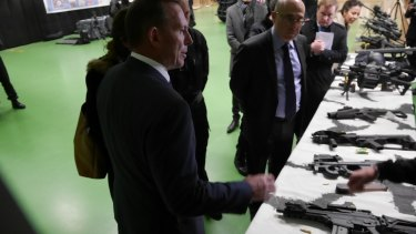 Australian prime minister Tony Abbott's inspects weapons at RAID's offices in France.