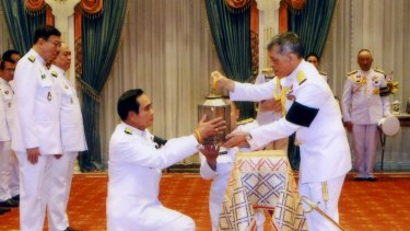 Thai King Maha Vajiralongkorn, right, passes the royal fire to Prime Minister Prayuth Chan-ocha to be used in ceremonies during the royal funeral and cremation of his father King Bhumibol last year.