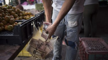 A fruit seller keeps 100-bolivar notes in a grocery bag at a fruit stand in Caracas on Monday.
