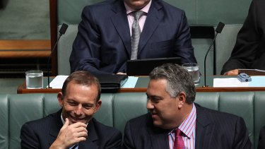 Tony Abbott and Joe Hockey share a moment in Parliament.
