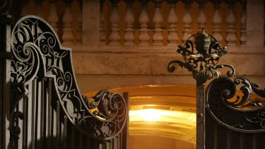 Protecting the Pope ... A member of the Swiss Guard closes the gate at the Arch of the Bells at St Peter's Basilica.
