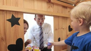 Opposition Leader Tony Abbott and Liberal candidate for Solomon have a tea party with Xavier Jones in a cubby house during a visit to the Mencshelyi household in the Darwin suburb of Lyons.