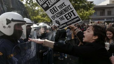 A protester yells at policemen outside the headquarters of state television ERT at Agia Paraskevi suburb north of Athens.