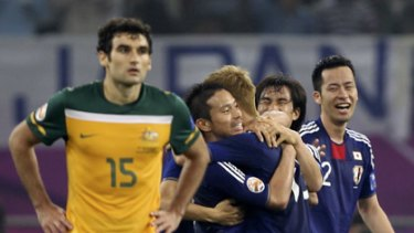 Japan players celebrate the winning goal as Australian midfielder Mile Jedinak ponders what might have been for the Socceroos.